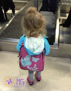 little girl with butterfly backpack at the airport