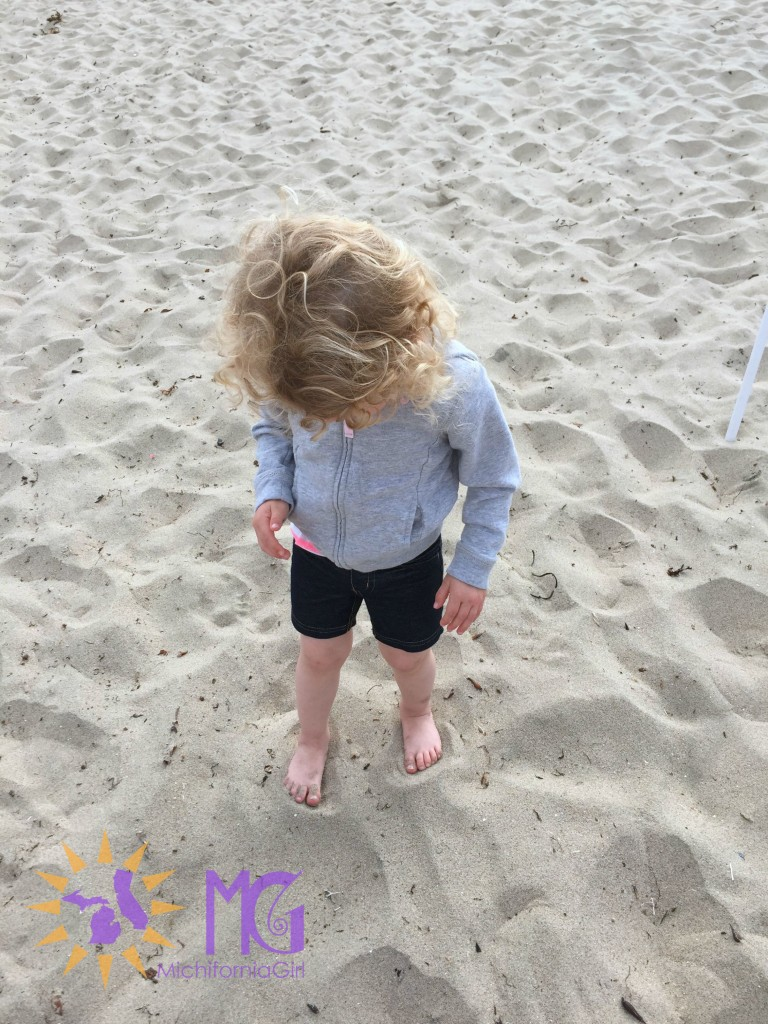 toddler with feet in sand on beach