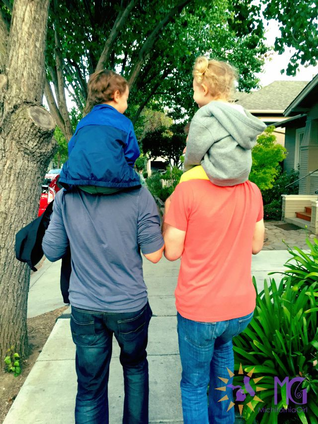 two kids on their dads' shoulders