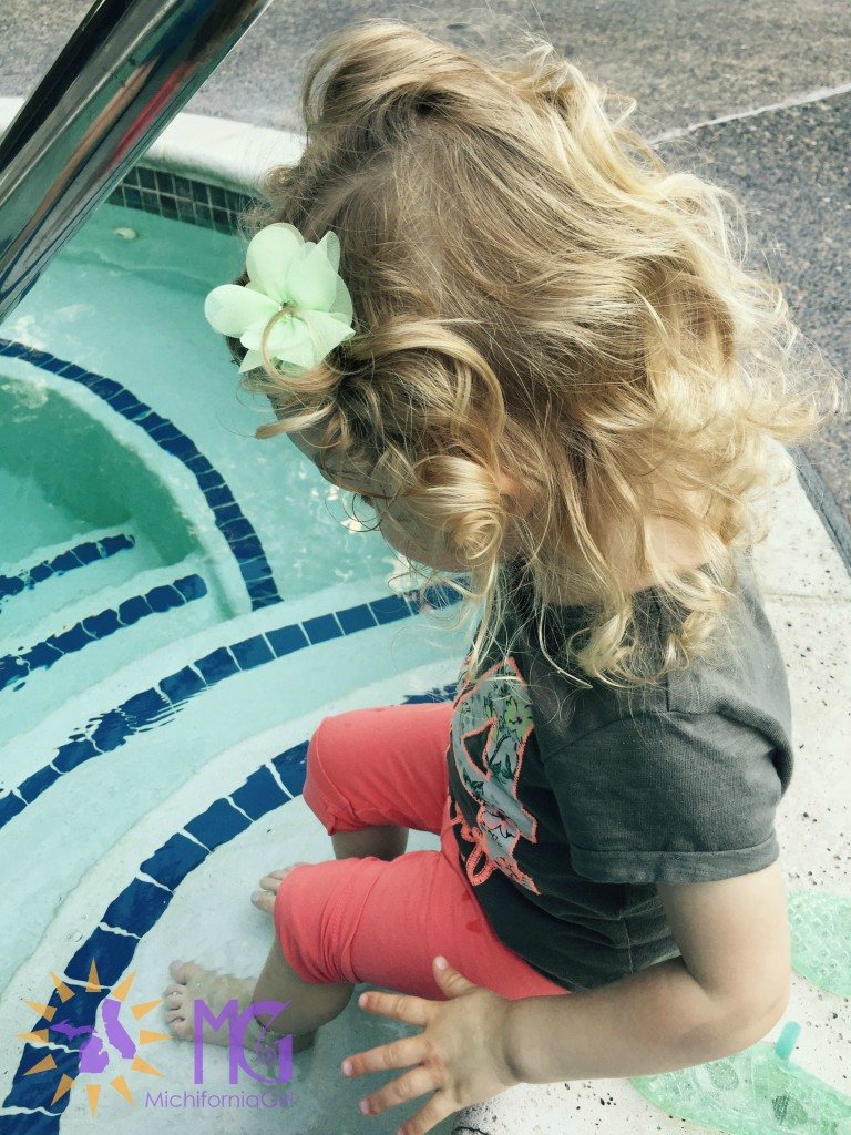toddler dipping feet in hot tub