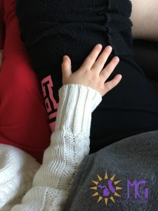 little girl's hand on mom's leg