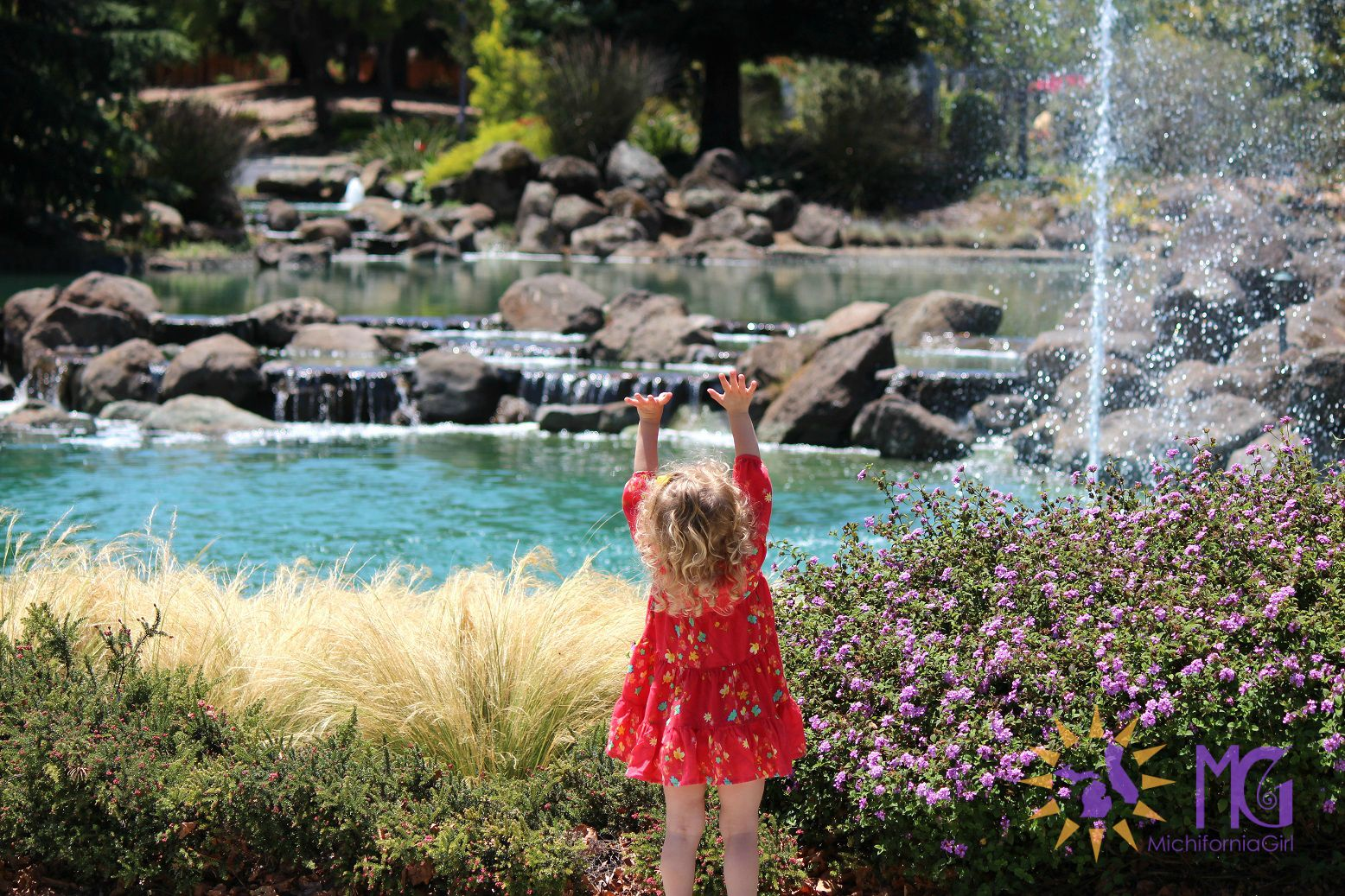 little girl stretching her arms toward water fountain
