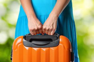 woman holding orange suitcase