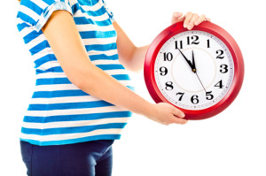 pregnant woman holding a clock waiting for baby