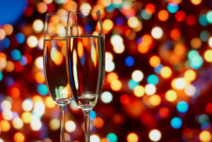 two champagne glasses with colorful lights in background