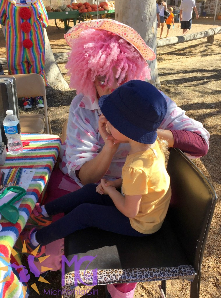 little girl getting her face painted by a clown