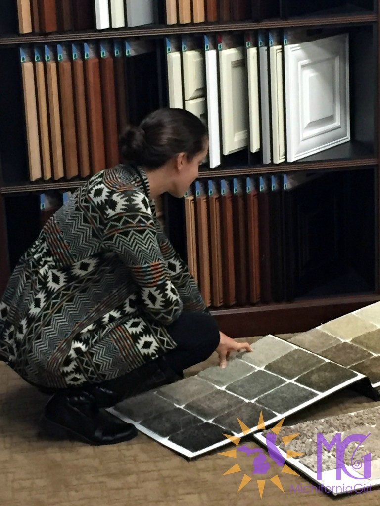 woman crouching down to check carpet samples at design center