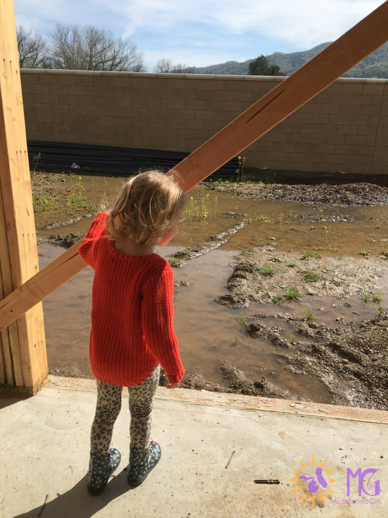 little girl staring at muddy backyard