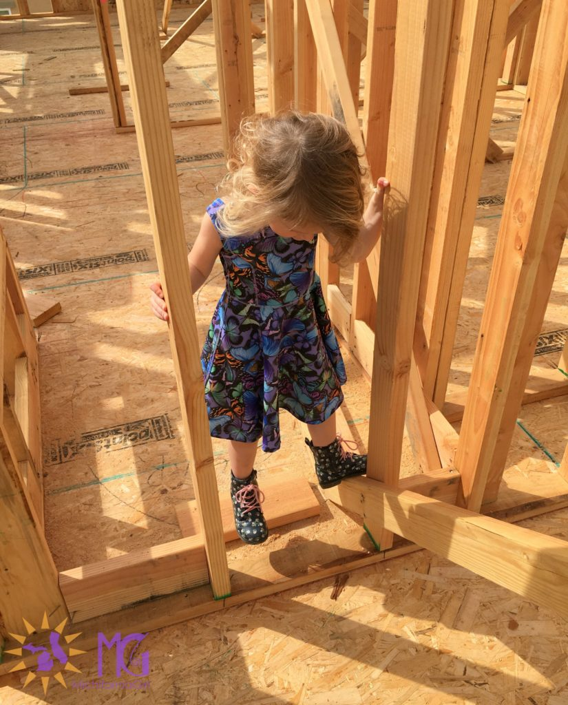girl climbing on new construction board frame