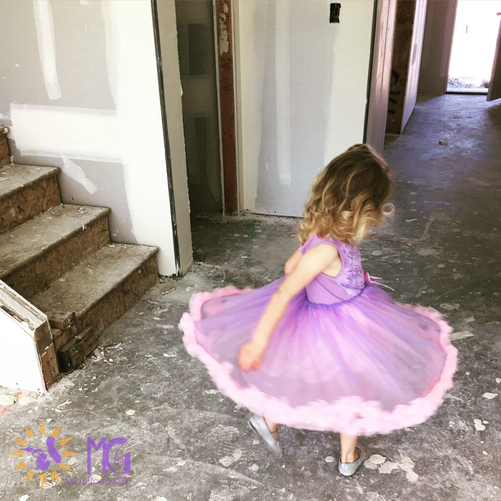 little girl twirling in a purple and pink dress at a new house construction site