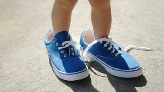 space between baby and boy baby feet in big shoes