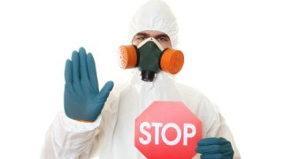 person in hazmat suit holding a stop sign sanitation chamber
