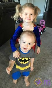girl and boy dressed up in halloween costumes as supergirl and batman diary of a dog