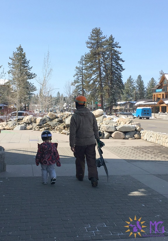 little girl with her dad walking with snowboards in tahoe